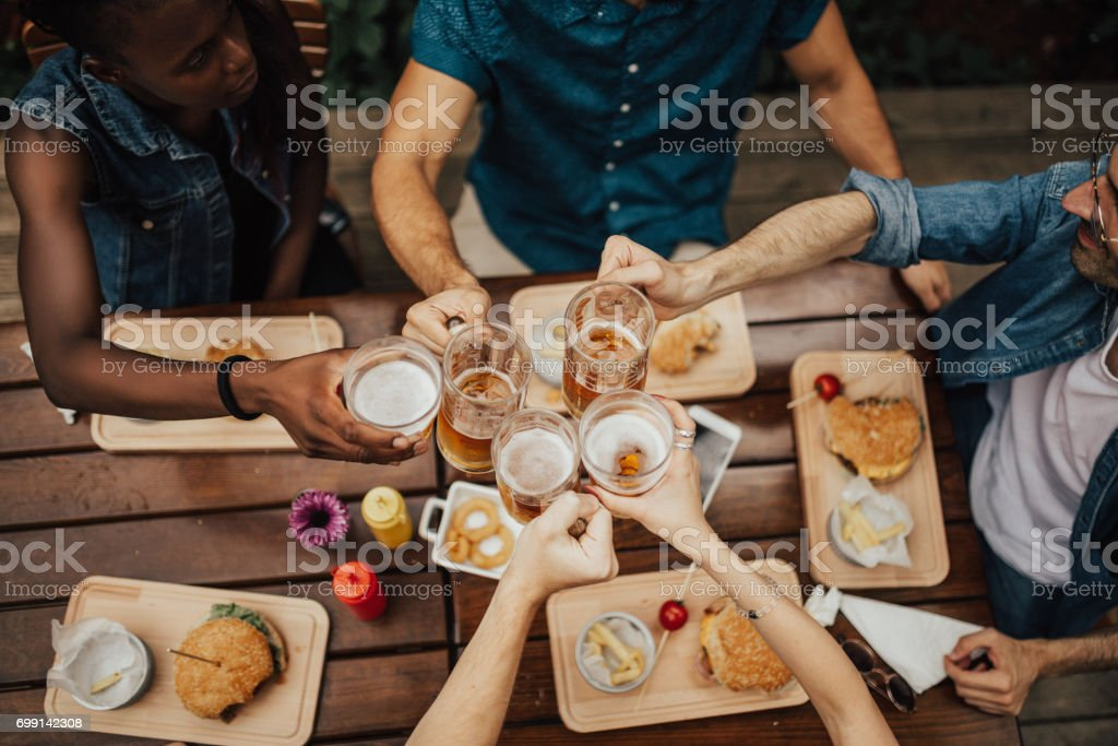 Multi-ethnic group of people raise their beer mugs stock photo