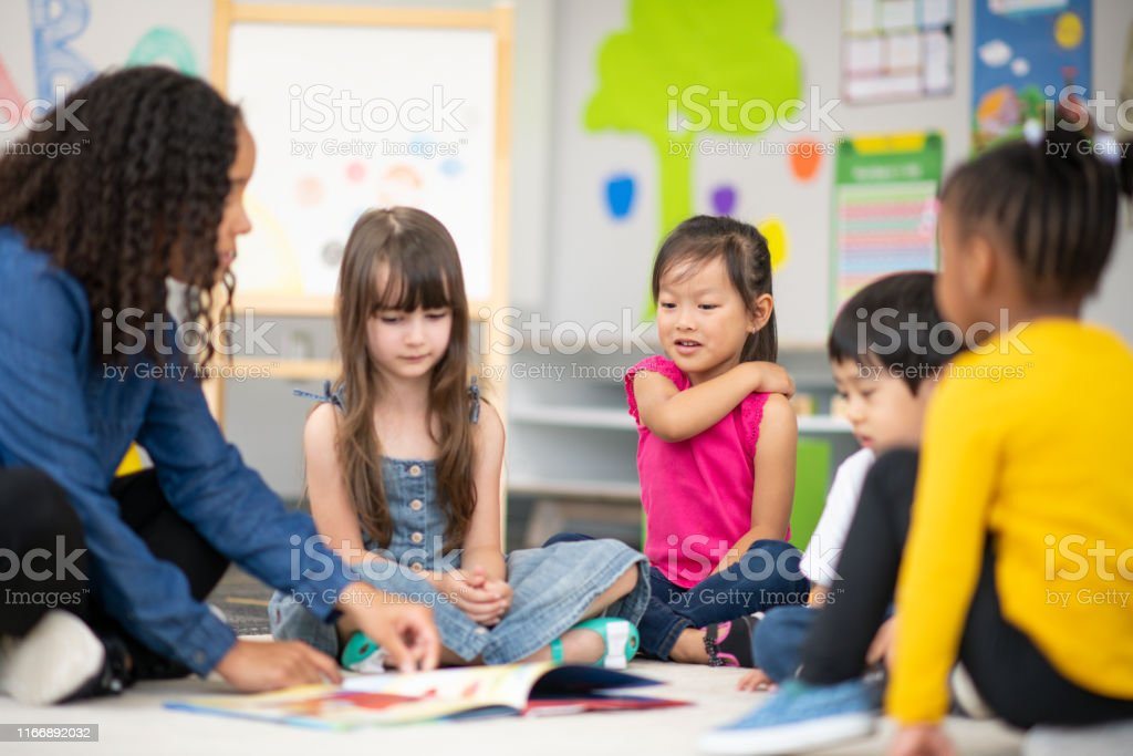 An ethnic teacher is sitting on the floor with a multi-ethnic group...