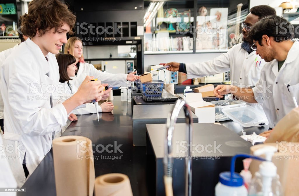 Multi-ethnic group of professors and students in college science laboratory. stock photo