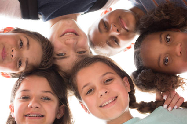 Multi-ethnic group of school children friends in huddle. stock photo