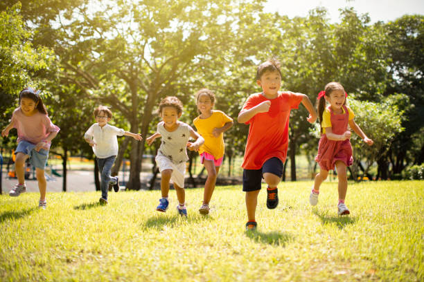 Multi-ethnic group of school children laughing and running Multi-ethnic group of school children laughing and running outdoors stock pictures, royalty-free photos & images