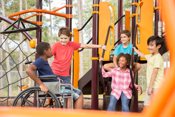 Multi-ethnic group of school children on school playground, one wheelchair. stock photo