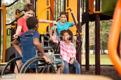 istock Multi-ethnic group of school children on school playground, one wheelchair. 864606702