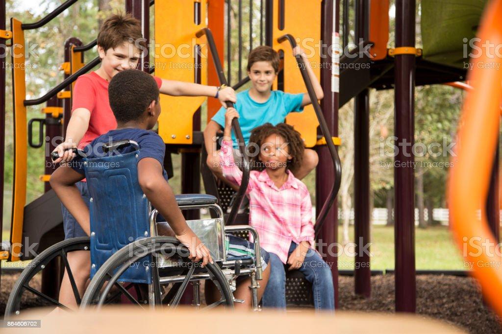 Grupo multiétnico de crianças em idade escolar no recreio da escola, uma cadeira de rodas. - foto de acervo