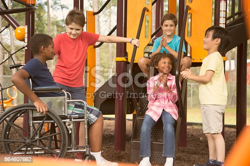 istock Multi-ethnic group of school children on school playground, one wheelchair. 864607662