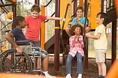 Multi-ethnic group of school children playing on school playground.  African descent, elementary age boy is in a wheelchair.  Other children, play and talk to boy in front of outdoor playground equipment.  Education in USA, exercise themes, differing abilities.