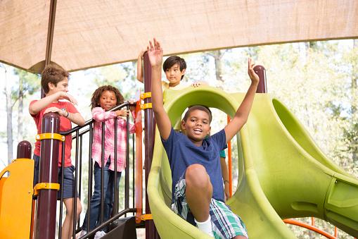 Multi-ethnic group of school children playing on school playground.