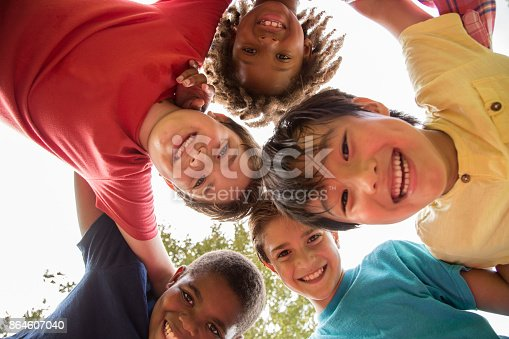 istock Multi-ethnic group of school children playing on school playground. 864607040