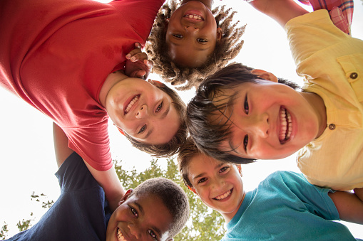 istock Multi-ethnic group of school children playing on school playground. 864607040