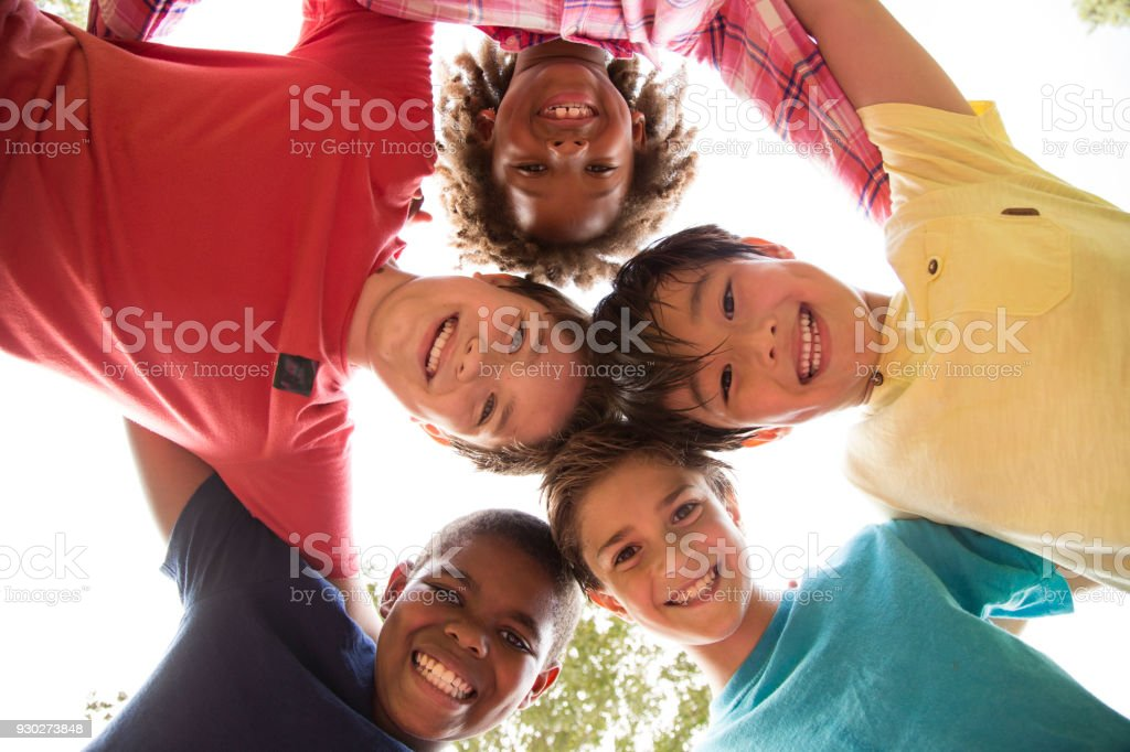 Multi-ethnic group of school children playing on school playground. stock photo