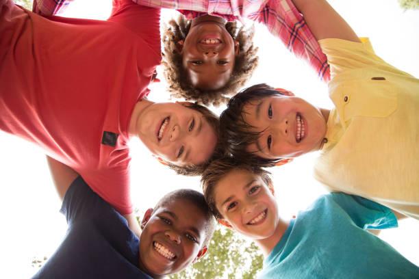 multi-etnische groep van school kinderen spelen op het schoolplein. - alleen kinderen stockfoto's en -beelden