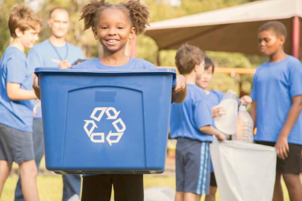 Multi-ethnic group of school children recycling at park. Multi-ethnic group of school children recycling and picking up trash at their local park, school playground.  The sports team of volunteers is happy to clean up their community.  African descent girl foreground holding recycling bin.  Other team members and soccer coach with trash bags in background. social responsibility stock pictures, royalty-free photos & images