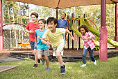 Multi-ethnic group of school children playing on school playground.  The group of friends excitedly run toward the next outdoor activity.  Education in USA, exercise themes.