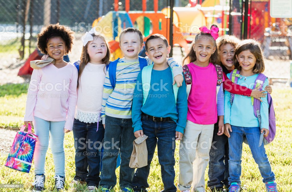 Multi-ethnic group of school children standing in a row stock photo