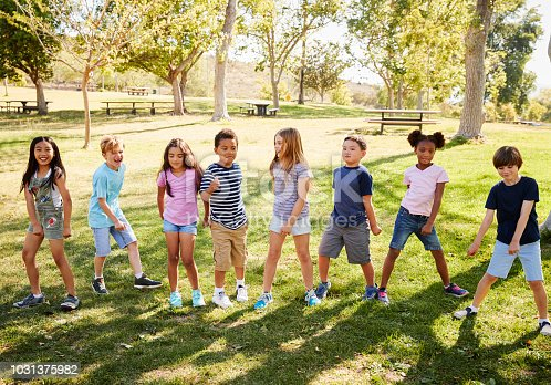 Multi-ethnic group of schoolchildren playing in park