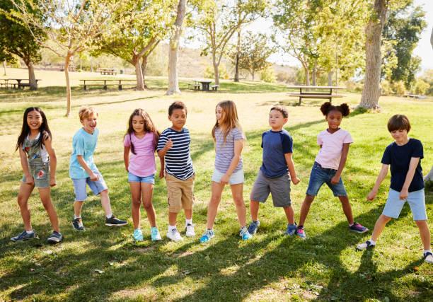 multi-ethnic group of schoolchildren playing in park - aree esterne della scuola foto e immagini stock