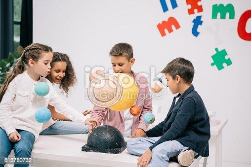 istock Multiethnic group of schoolchildren working with solar system model in classroom 813780732