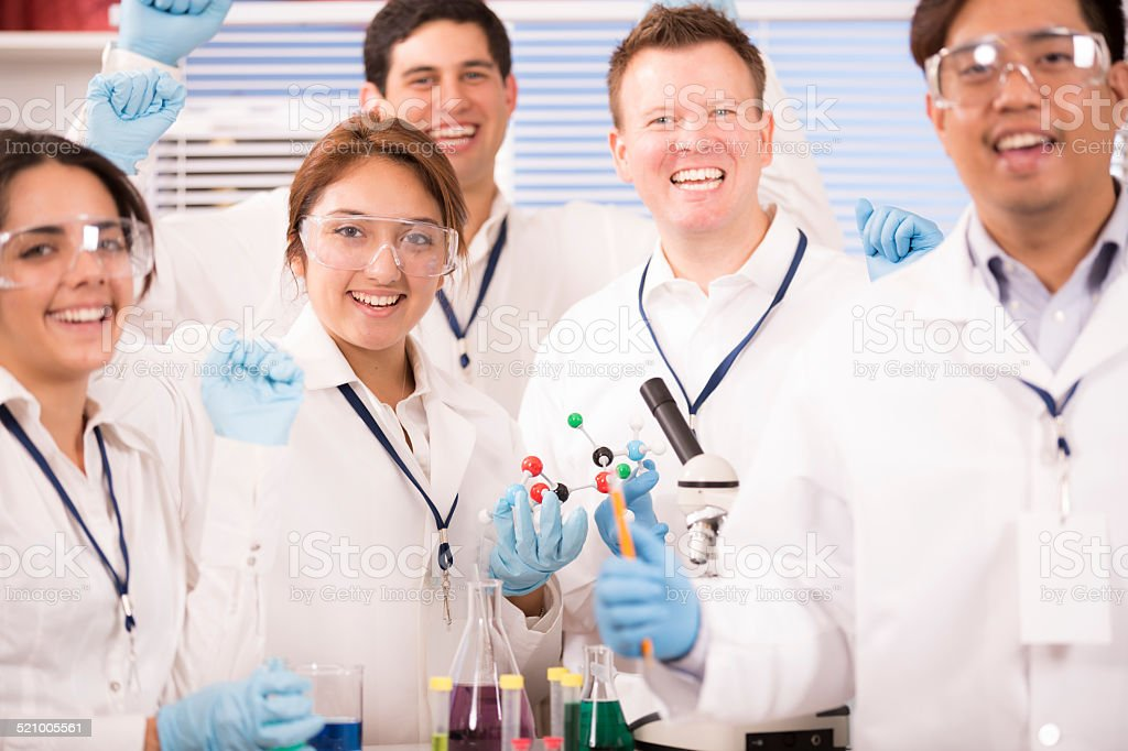 Multi-ethnic group of scientists in research laboratory. Excited about discovery. stock photo
