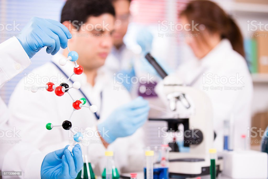 Multi-ethnic group of scientists in research laboratory. Science experiments. stock photo