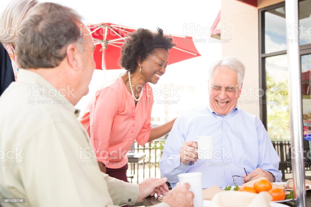 Multi-ethnic group of senior adult friends enjoy visiting at outdoor cafe. stock photo