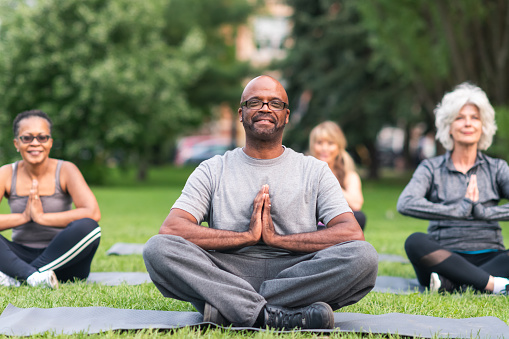 A multi-ethnic group of seniors is attending a yoga class outdoors. The group is sitting on yoga mats. They are meditating. The individual in focus is a black man. He is sitting at the front of the group. He is smiling directly at the camera.