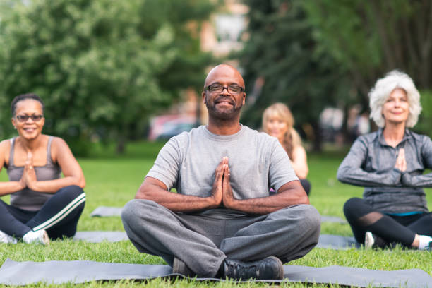 multi-ethnic group of seniors meditating outdoors - meditation stock pictures, royalty-free photos & images