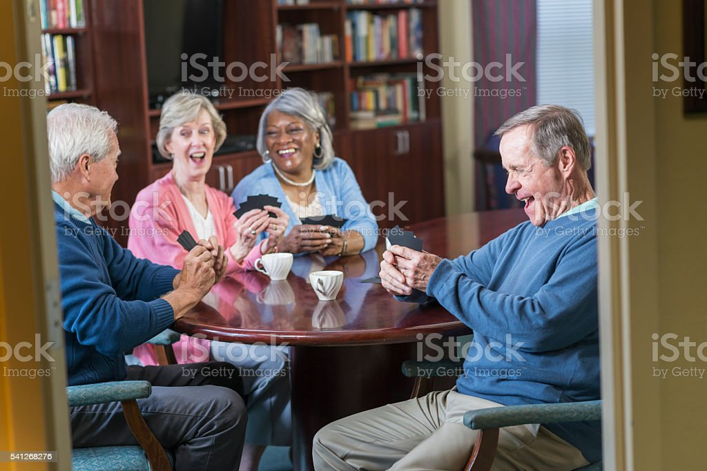Multi-ethnic group of seniors playing card game stock photo