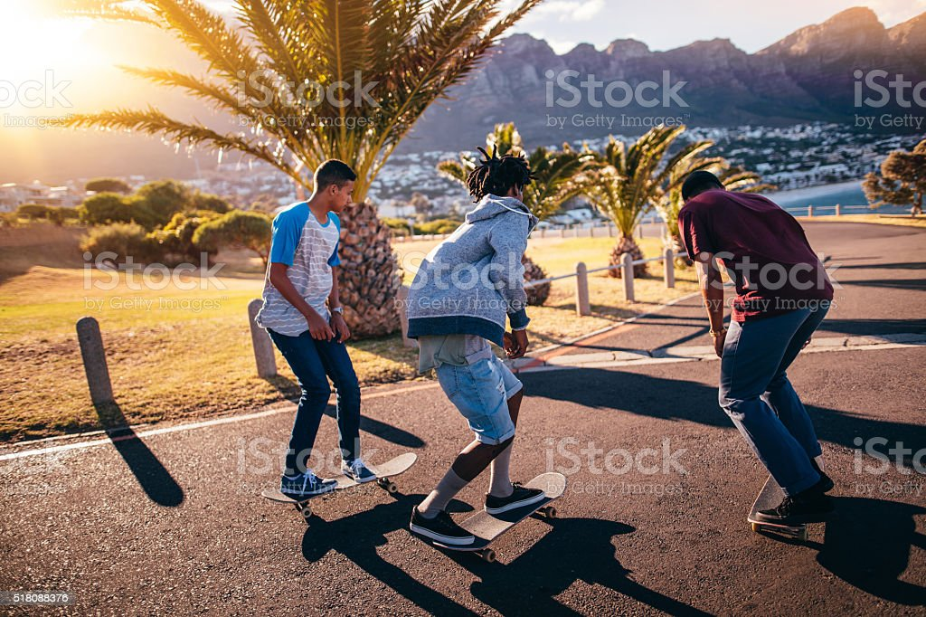 Multi-Ethnic Group of Skaters Skateboarding Down Street at Seasi stock photo