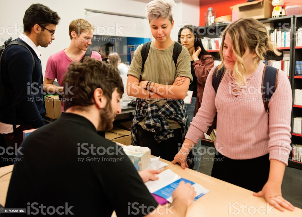 Multi-ethnic group of students buying books in student association classroom. stock photo