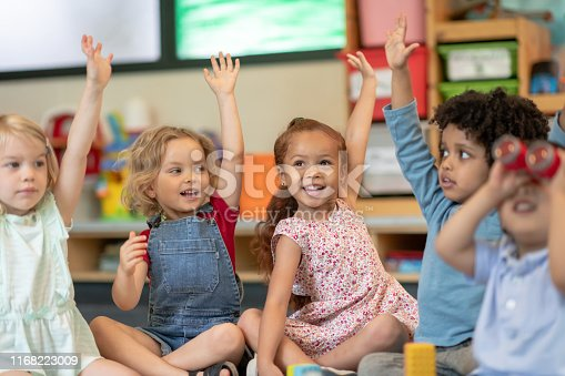 A multi-ethnic group of preschool students is sitting with their legs crossed on the floor in their classroom. The teacher is sitting on the floor facing the children. The happy kids are smiling and listening to the teacher. They have their arms raised and are eager to answer the teacher's question.