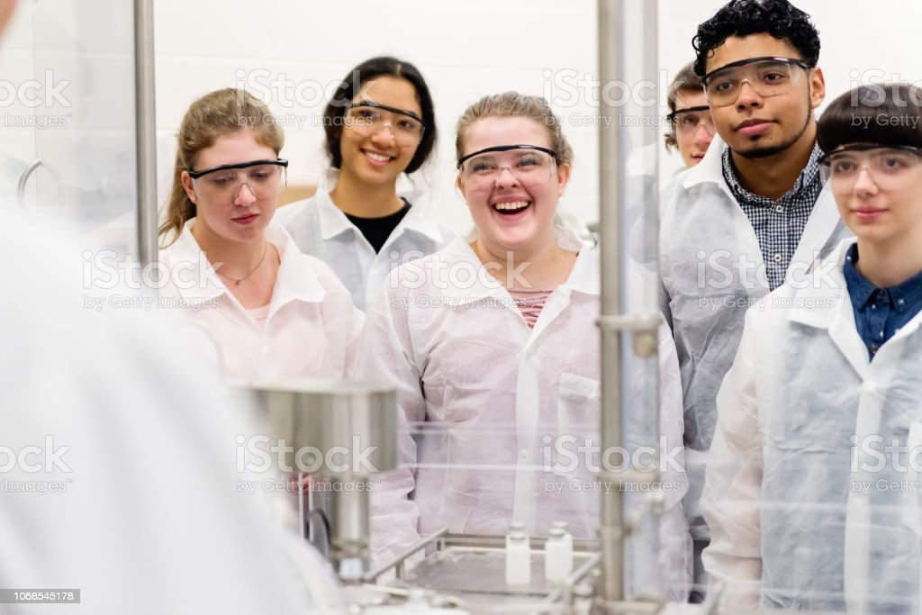 Multi-ethnic group of students in College pharmaceutical laboratory. stock photo