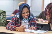 A multi-ethnic group of students sits in a lecture hall listening to their professor off-screen. They are taking notes with the focus being on a female of Indian descent wearing a hijab.
