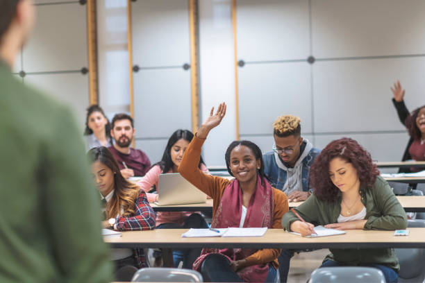 A multi-ethnic group of students listening to presentations stock photo