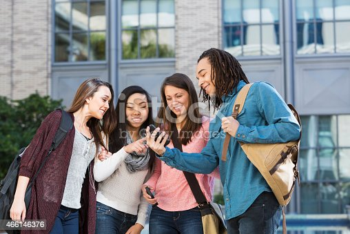 143071438 istock photo Multi-ethnic group of students outdoors with phone 466146376