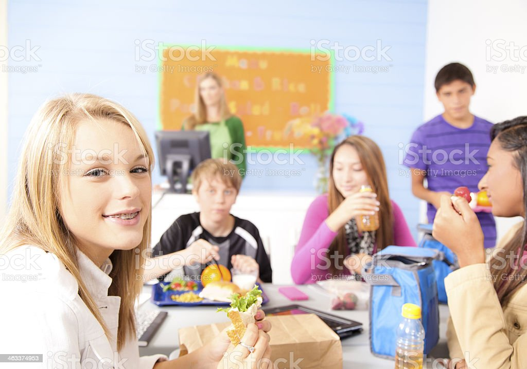 Multi-ethnic group of teens in school cafeteria eating lunch. stock photo