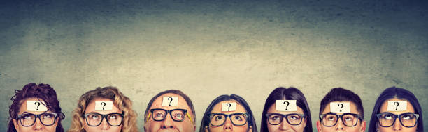 Multiethnic group of thinking people in glasses with question mark looking up stock photo