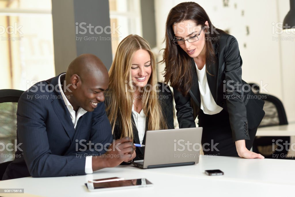 Multi-ethnic group of three businesspeople meeting in a modern office. stock photo