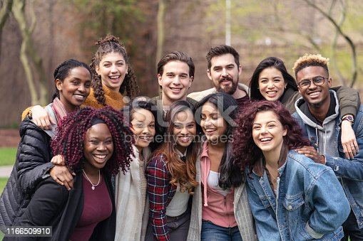 A large sized group of university-aged students, both male and female, are standing out on the campus lawn and smiling into the camera in this educational portrait.They are carefree.