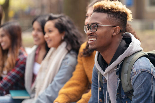 Multi-Ethnic Group of University Students Relaxing Outside A middle-sized group of university-aged students, both male and female, are sitting outside on the campus grounds and relaxing before class. They are dressed in casual but stylish clothing while smiling. college fair stock pictures, royalty-free photos & images