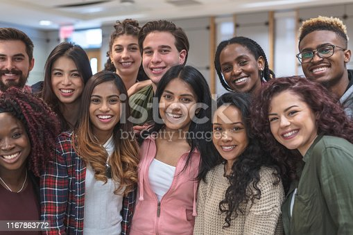 A large-sized group of university-aged students, both male and female, are standing inside the school while relaxing before class. They are dressed in casual but stylish clothing while smiling in this portrait.