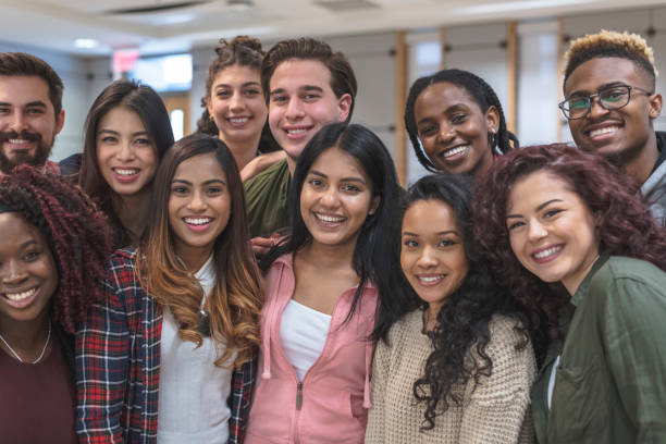 Multi-Ethnic Group of University Students Sitting Inside Together A large-sized group of university-aged students, both male and female, are standing inside the school while relaxing before class. They are dressed in casual but stylish clothing while smiling in this portrait. college fair stock pictures, royalty-free photos & images