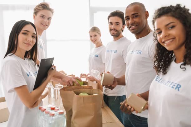 multiethnic group of volunteers - volunteer stock photos and pictures