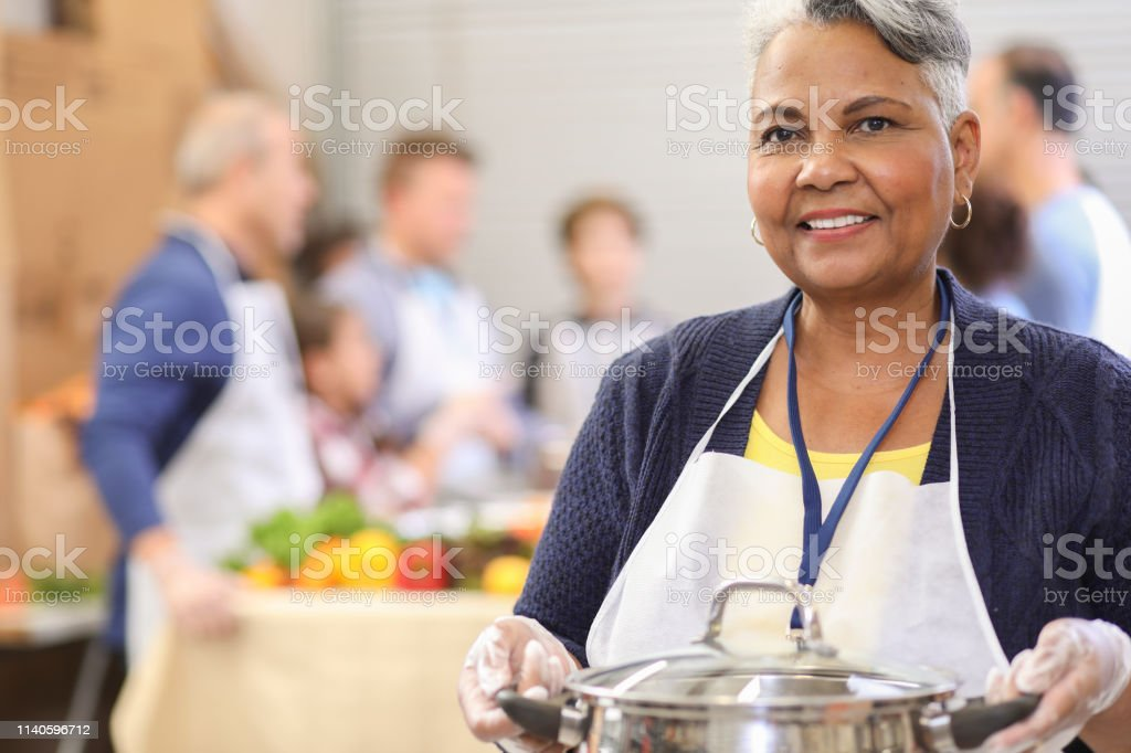 Multi-ethnic, mixed age group of volunteers serves food at a soup...