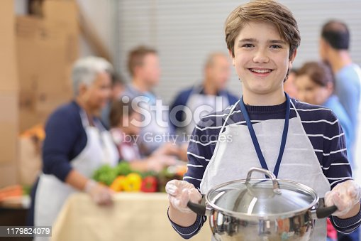 istock Multi-ethnic group of volunteers serves food at soup kitchen. 1179824079