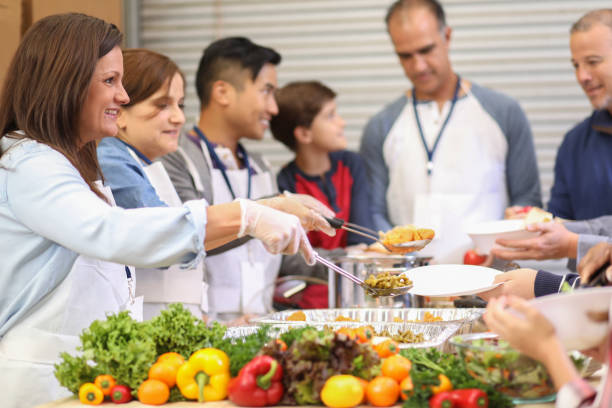 Multi-ethnic group of volunteers serves food at soup kitchen. stock photo