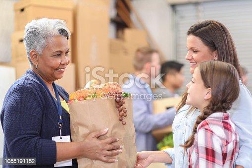 istock Multi-ethnic group of volunteers work at food bank. 1055191152