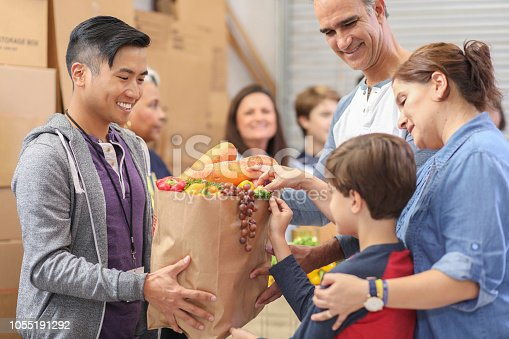 Multi-ethnic, mixed age group of volunteers work together at food bank.  They pack sacks and boxes of food for needy people in their community.  Man gives sack full of groceries to needy family.