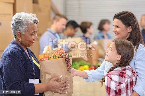 istock Multi-ethnic group of volunteers work at food bank. 1128250393