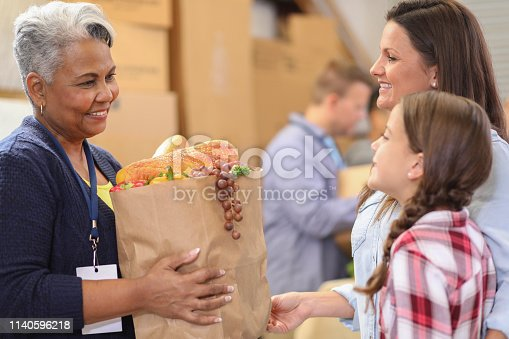 istock Multi-ethnic group of volunteers work at food bank. 1140596218