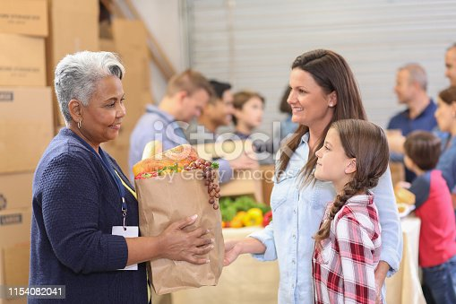 istock Multi-ethnic group of volunteers work at food bank. 1154082041